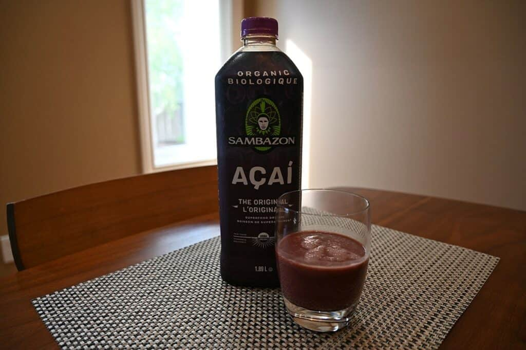 Costco Sambazon Acai Superfood Drink  poured in a glass beside the bottle