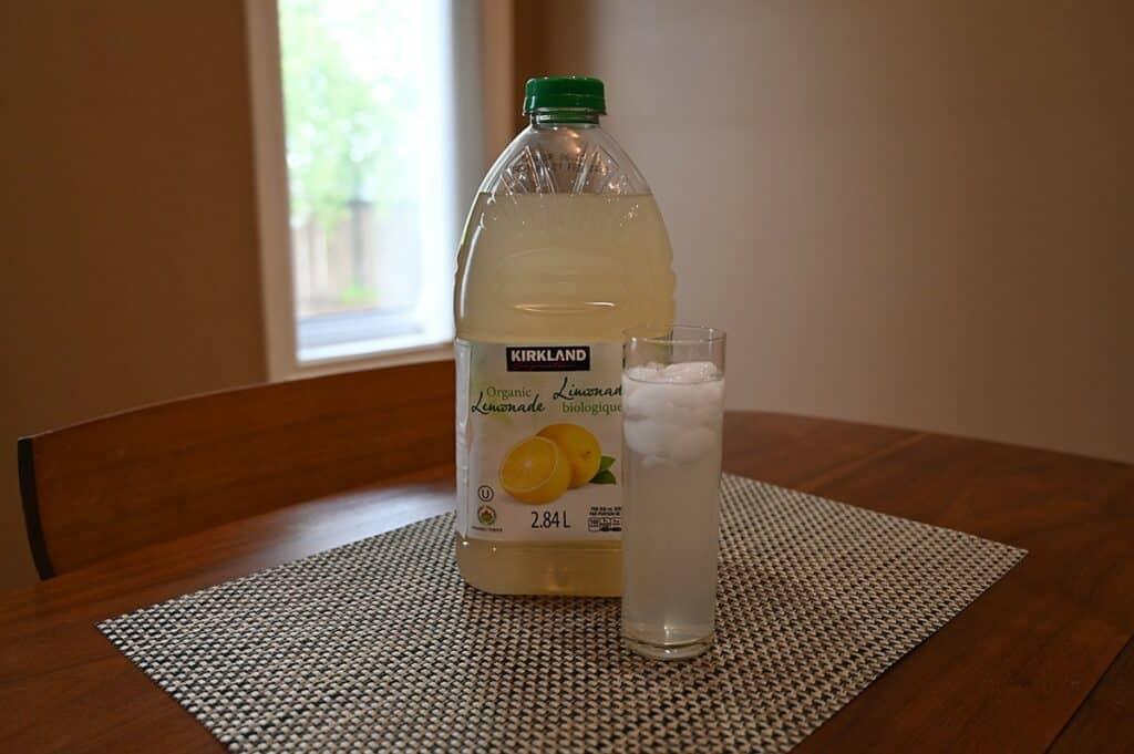 Costco Kirkland Signature Lemonade poured in a glass beside the bottle