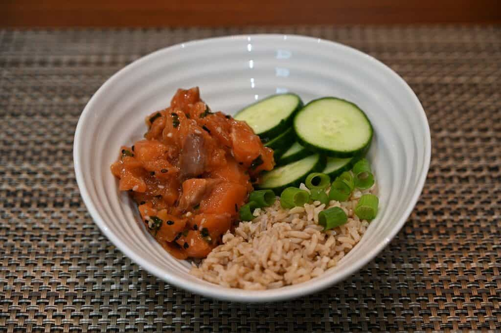 Costco Dom Reserve Singles Steelhead Salmon Poke in a bowl with rice, green onion and cucumber.