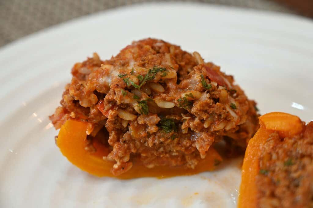 A close-up of a stuffed pepper cut in half to show the filling.